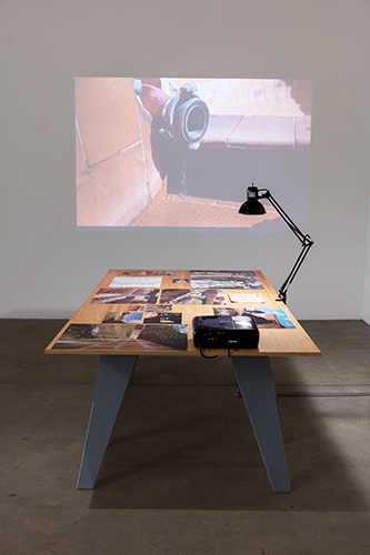 This artwork installation by the artist Felipe Dulzaides features a video projection and a table with an assortment of photographs and notes. The video still depicts a a close up of a water hose located in the Cuban National Art Schools. The photographs and notes on the table also feature the Cuban National Art Schools.
