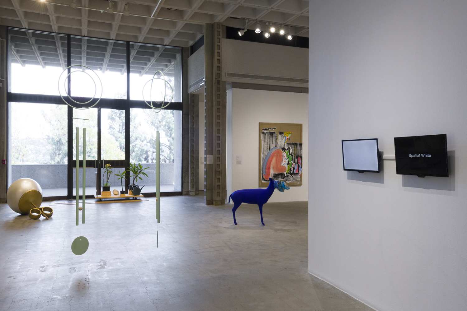 There are two light green sculptural chime works hanging from the ceiling by the artists Rebecca Bruno and Mak Kern. Behind this work to the left is a large sculpture depicting a pearl stud placed on the floor by the artist Alex Nazari. To the right of this artwork is an installation of plumeria plants on a wooden dolly by the artist David Horvitz. To the right of this work is a large abstract painting with various shades of pink, black, blue and green on brown canvas by the artist Lindsay August-Salazar. In front of this artwork is a sculpture depicting a cobalt-blue deer with a plastic chips bag over its head by the artists Galería Perdida. And in front of this work is a video artwork on two TV monitors by the artists pecking nets. One TV monitor has a blank white screen and the other TV monitor has a black screen with the words Spatial White.
