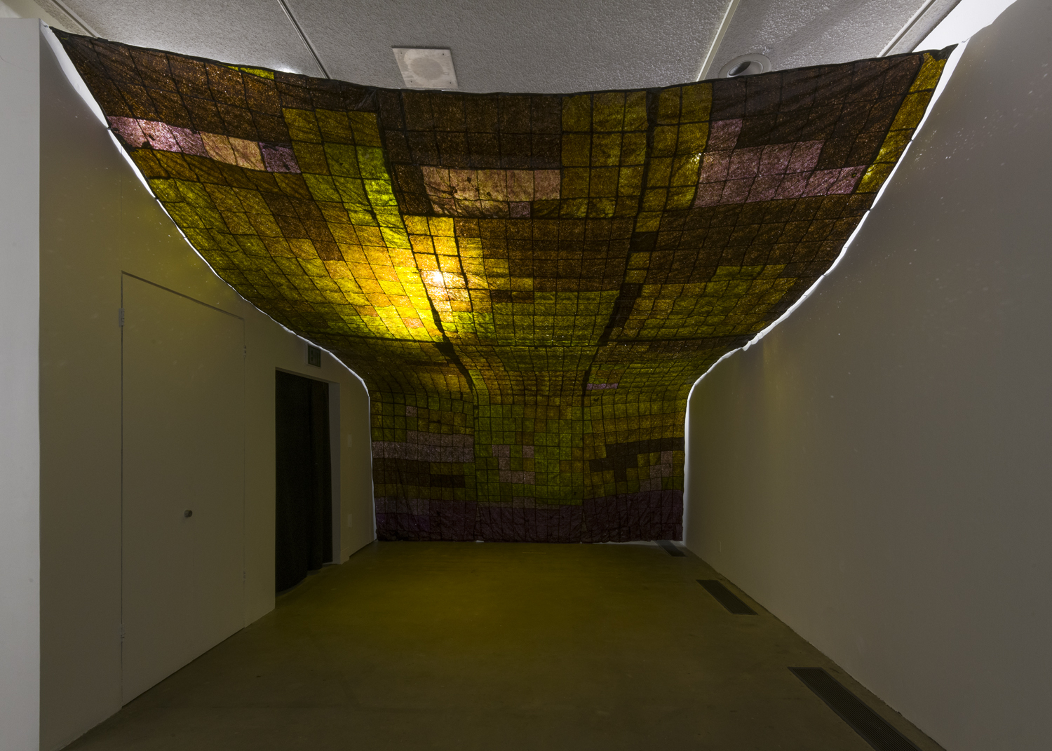 This artwork installation by the artist Hannah Varamini is comprised of various colored seaweed squares stitched together to form a canopy. The canopy covers the ceiling and the far back wall of the room.