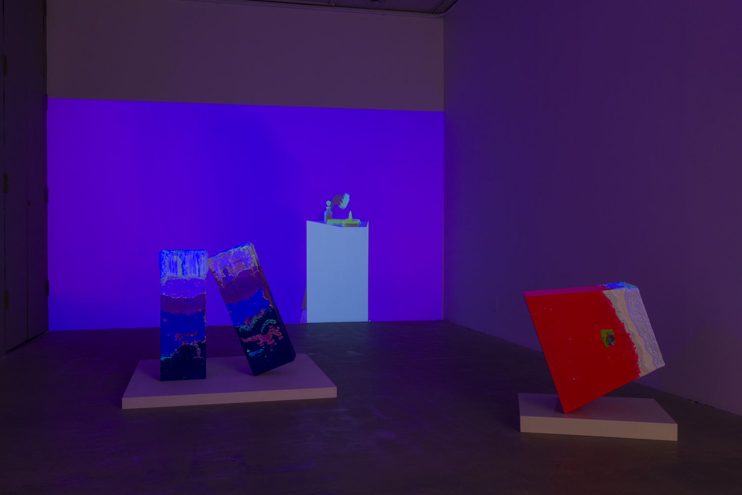 In this artwork installation by the artist Lena Daly, a flourescent, neon colored video projection is displayed on a wall. This video projection still features an image of a small sculptural work on a pedestal.