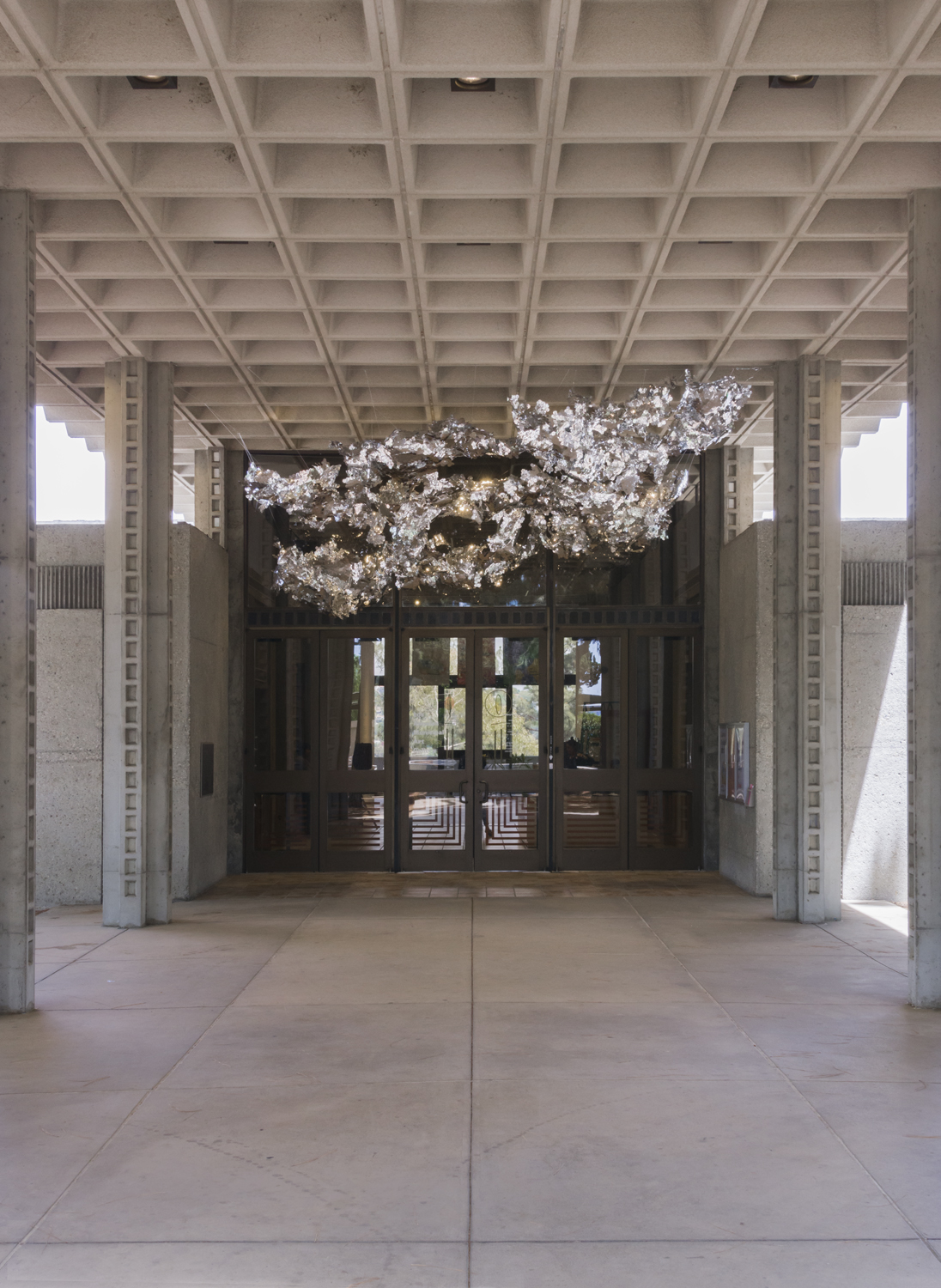 This is an artwork by the artist Olga Lah featuring silver, reflective material in a cloud-like shape hanging above the gallery's entrance doors outside.