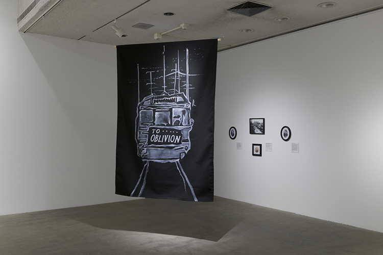 In this artwork installation by the artist Sandra de la Loza, a black banner hangs from the ceiling with a white drawing of the back of a train and the words To Oblivion. Behind this work are small, black and white portraits of figures from the Pacific Electric Railway Strike of 1903.