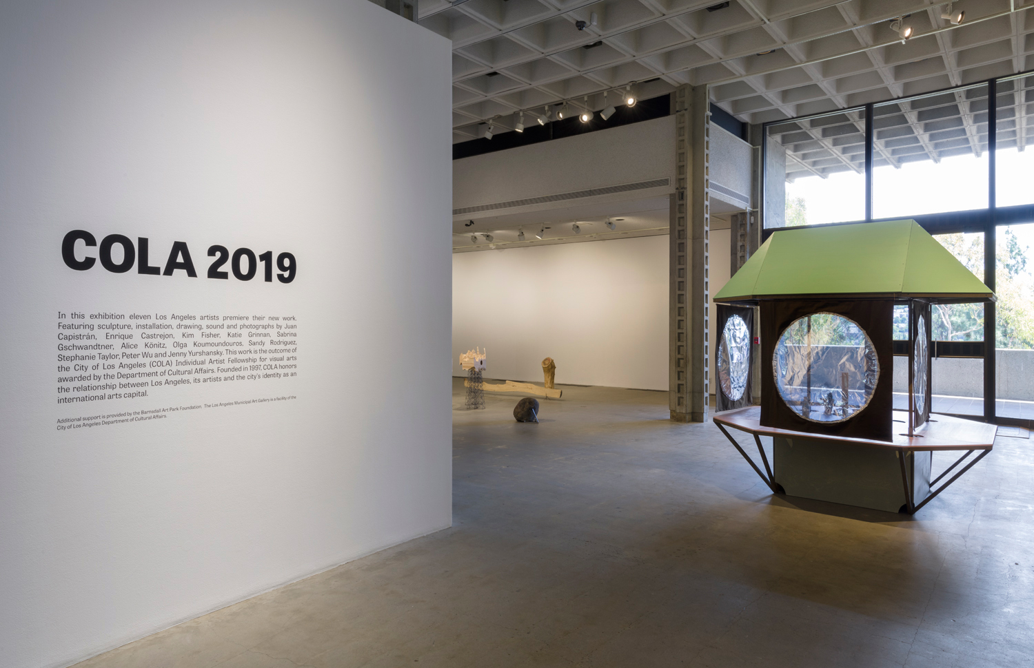 There is a large artwork installation by the artist Alice Könitz of a survivalist structure. This structure includes an angular light green roof and three different hanging fabric panels with circular reflective material in the middle of each panel. These three panels are on three of the sides of the four-sided structure. There is also a flat surface for seating and angular bars to support this surface. To the left of this structure is another artwork installation by the artist Katie Grinnan of a tree plank placed on the floor and a large rock placed on the floor.