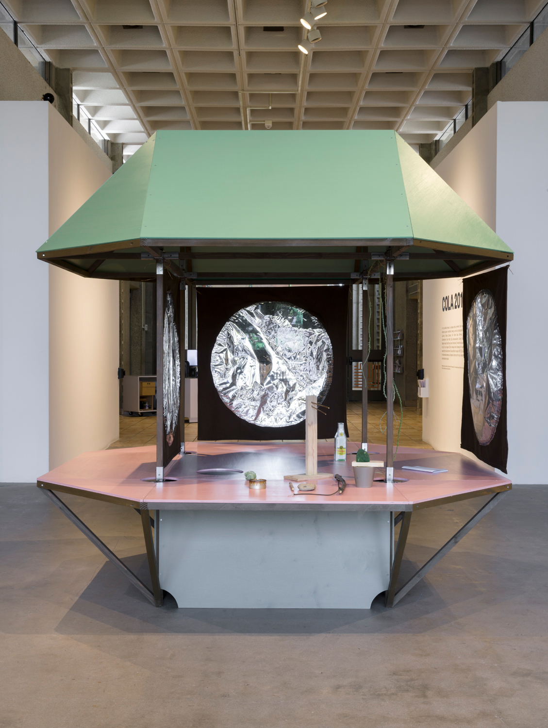 This artwork installation is a survival structure by the artist Alice Könitz. The structure includes an angular, light green roof and three hanging fabric panels with a circular reflective material in the middle of each panel. There is also a light pink, flat seating surface beneath the panels. On this seating surface are an assortment of objects, including a wooden bar propped upright, a paper object resembling a bottle of Topo Chico, a cacti in a pot, a rock, a small ball of yuca, and a dark piece of wood with string attached. There are also three different covered holes on this surface. Beneath this surface is a rectangular support with metal bars supporting the pink surface and structure overall.