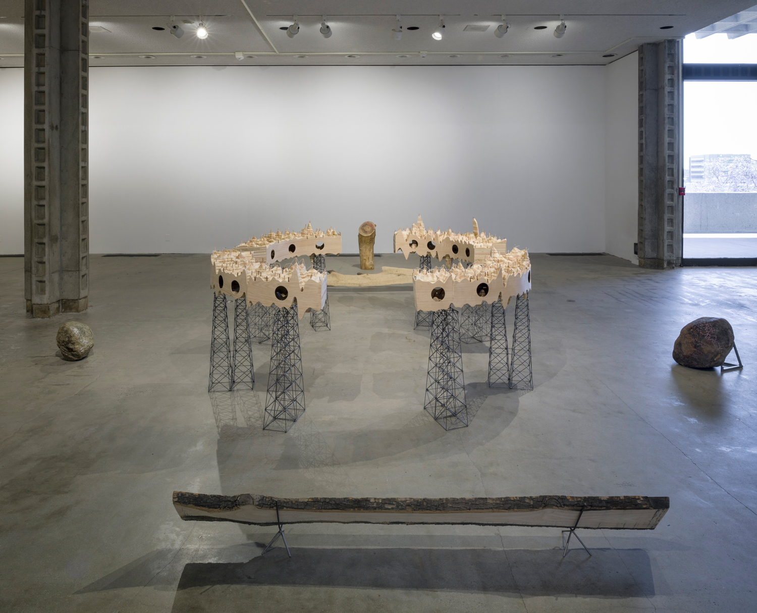 In this artwork installation by the artist Katie Grinnan, there is a large, circular wooden structure with metal stands placed in the center. The wooden structural part has a canyon-like appearance, and has circular cut-outs on the sides. On both the left and right sides of this structure, there is a large rock placed on the floor supported by a metal stand. In front of the wooden structure, there is a large, flat, wooden plank propped up and close to the ground with two small metal stands. Behind the wooden structure is a tree trunk and another large, flat, wooden plank propped up and close to the ground with two small metal stands.