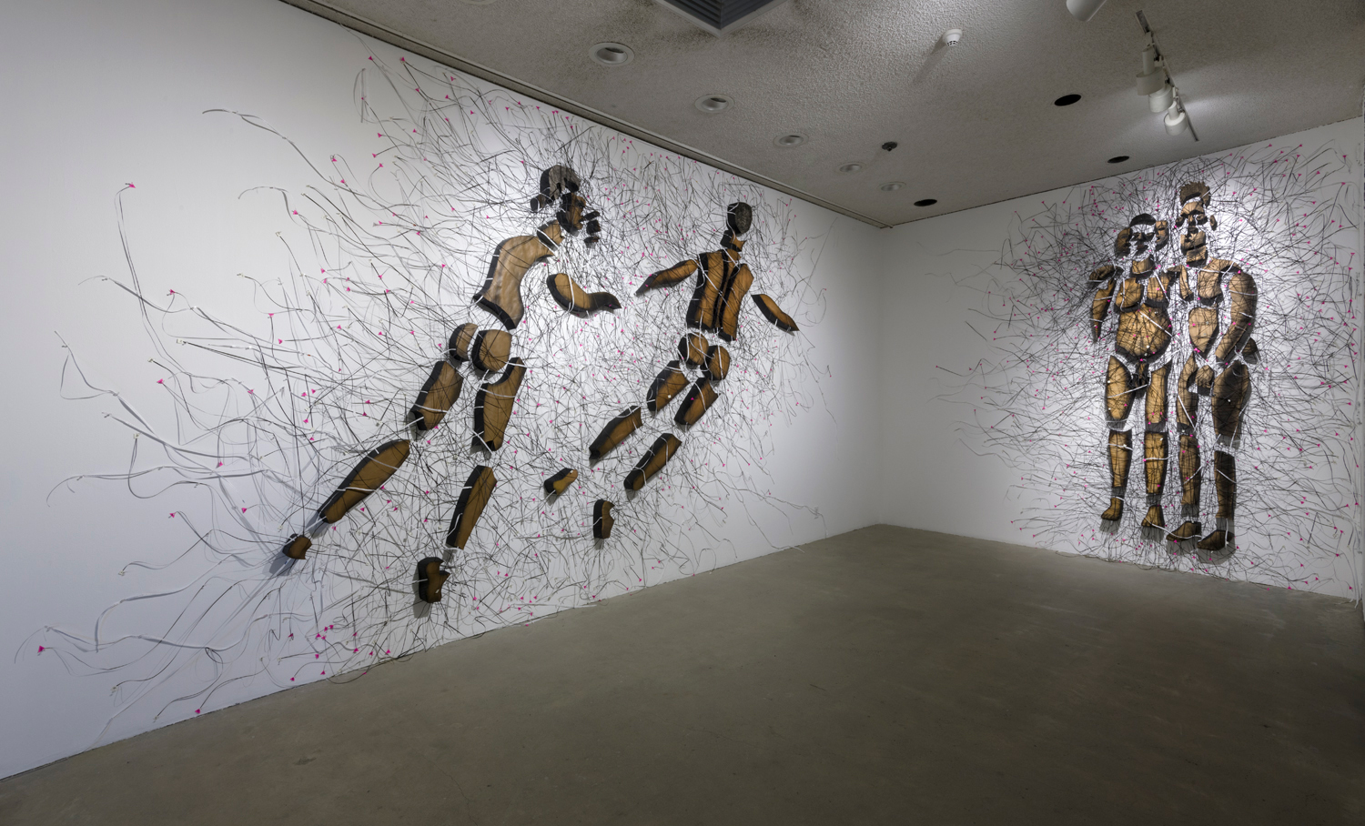 In this artwork installation by the artist Enrique Castrejon, there are a total of four figural sculptures hanging on the walls. There are two figural sculptures depicting naked men of color, with a small amount of space in between each body part on one wall. These two bodies are angled to the right of the wall as if they are in motion. There are also various strands of string attached to these figures. To the right of these sculptures are two more figural sculptures hanging on the wall. These sculptures also depicted naked men of color, and are placed very close to each other and appear to be holding each other. There are also various strands of string attached to both figures, and there is also a slight amount of spacing in between their body parts.