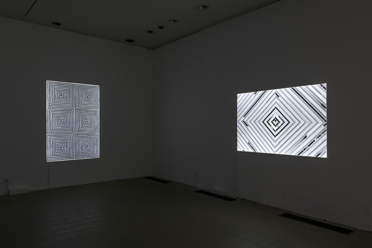 This artwork installation by the artist Sabrina Gschwandtner features one artwork hanging on the wall. This vertical artwork includes a quilt-like pattern of six different squares using black and white film strips on top of a lightbox. To the right of this work is another artwork. This horizontal artwork includes a triangular, quilt-like pattern also using black and white film strips. These film strips are mort spaced out in between each strip, so the light from the lightbox is more visible.