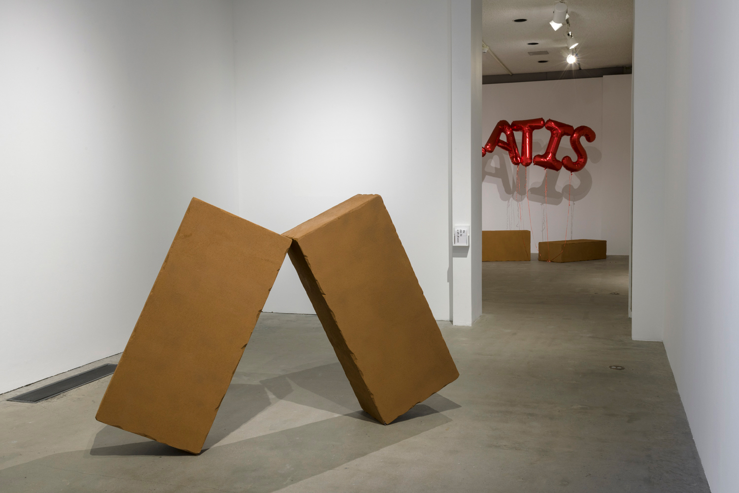 In this artwork installation by the artist Juan Capistrán, there are two large faux brick sculptures leaning against each other. Behind these works in the next room, there are two more faux brick sculptures placed on the ground. Attached to these sculptures are red, metallic balloons that say