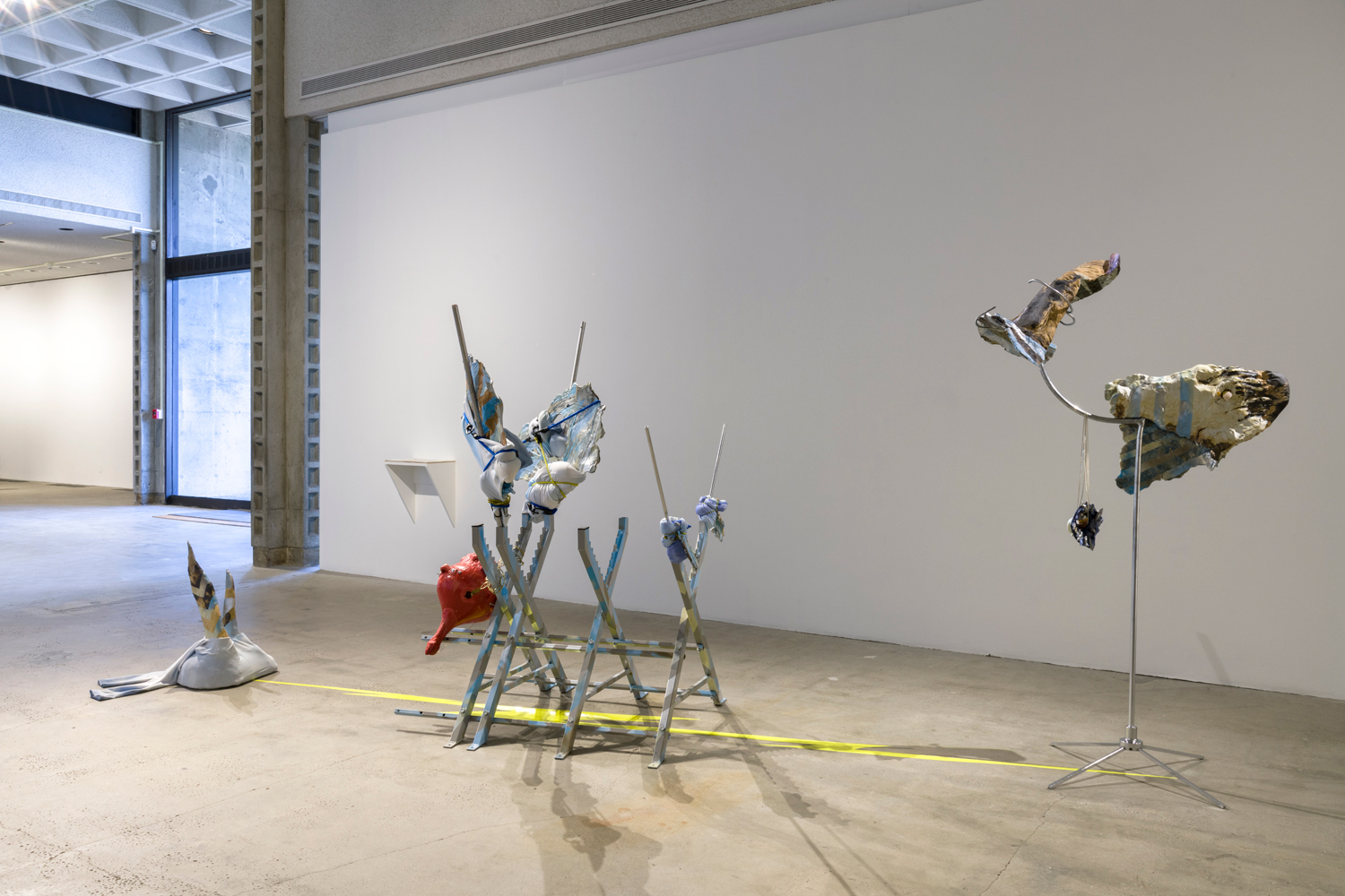 This artwork by the artist Olga Koumoundouros is a large sculpture depicting a flying fish. The sculpture is separated into three parts: one part depicts the tail of a flying fish made out of ceramic and with sky patterned leggings over it. The tail points up to the ceiling. The second part depicts the torso of a flying fish made out of four grey saw horses with painted blue stripes. There is also a red ceramic sculpture attached to the saw horses depicting the genitalia of the fish, as well as another sculpture depicting the