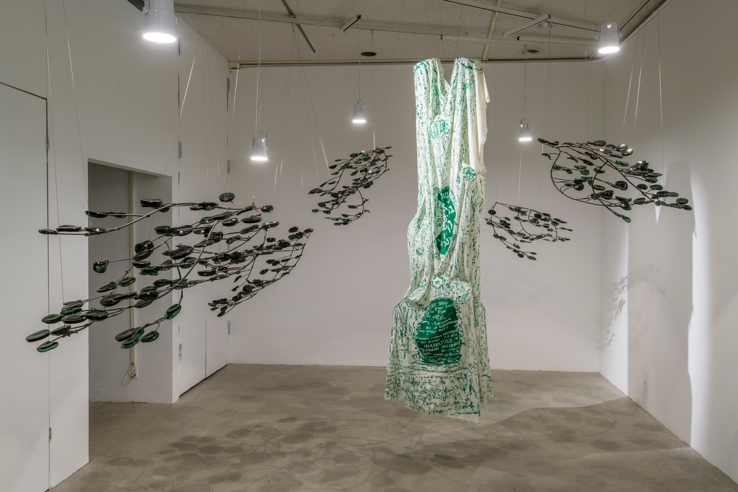 In this artwork installation by the artist Jenny Yurshansky, there are six sculptures depicting tree branches with leaves hanging the ceiling. The branch part of the sculpture is made of metal, and the leaves are made of dark green optometric glass. These sculptures are hanging and placed to surround another sculpture hanging in the center. This sculpture depicts a tree with no branches, with a white cloth draped over it. The white cloth has several embroidered texts in Yiddish and patterns in a forest-green color.