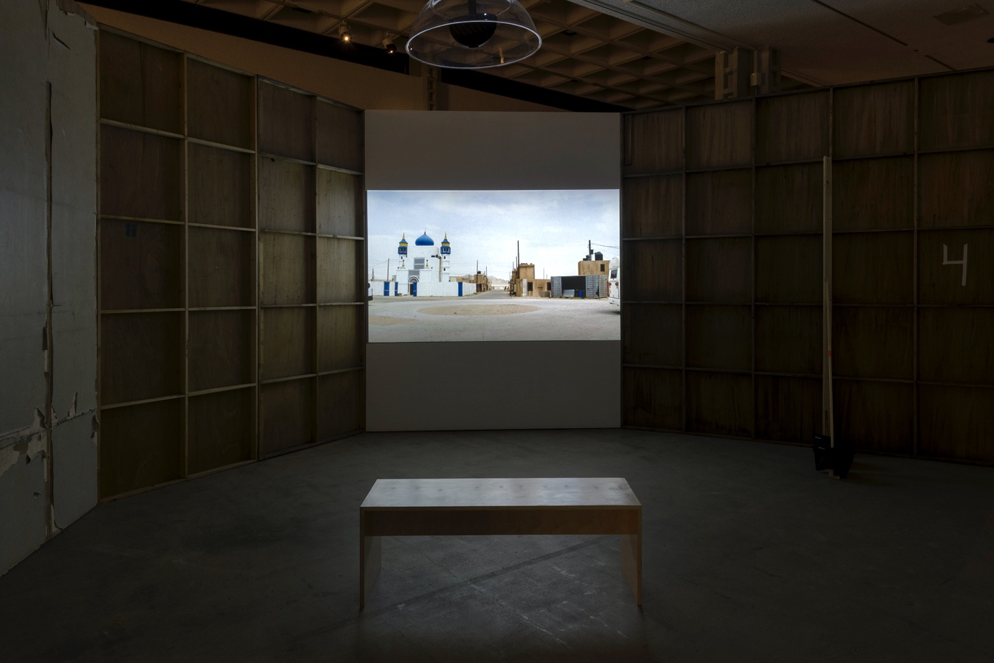 The artwork by the artist Abigail Raphael Collins includes tall wood walls with a projection screen displaying a video still. The video still features two different building structures with clouds and a blue sky in the background. The left structure is the Middle Eastern styled building and the right structure is the wooden military-like building.