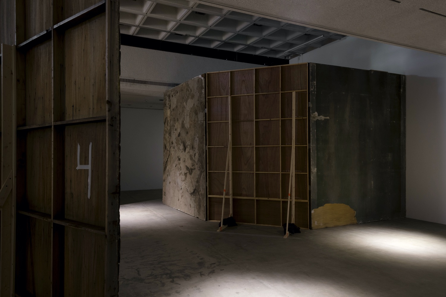 A featured art video installation set-up by the artist Abigail Raphael Collins has three tall wooden walls. The far left wooden wall is painted grey and has a rough, seemingly rocky surface, the middle wall is a grid of wooden squares with two long wooden beams along with black sandbags for support, and the far right wall is painted a darker grey with a large piece of paint missing in its bottom left corner. Another art video installation is located in the far left of the image, which has a wooden wall and white colored written number 4.