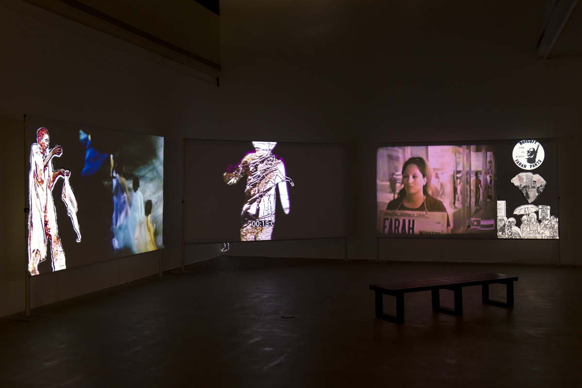 The artwork by the artist T. Kim-Trang Tran has three medium sized screens displaying different photos on each screen. Far left screen displays people dressed in red and orange and blue and yellow outfit walking and holding a cloth. The middle screen displays an up close person wearing a loosely red outfit walking behind a person with their left arm slightly raised. The far right screen displays a woman with a protest sign that reads