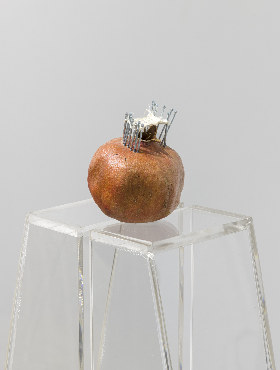 This artwork installation by the artist Alexandre Dorriz includes a clear pedestal with a pomegranate sculpture placed on top. The pomegranate is rust colored, with several silver metal pins placed in a circle on top of it. There is white fiber looped around and in between the metal pins.