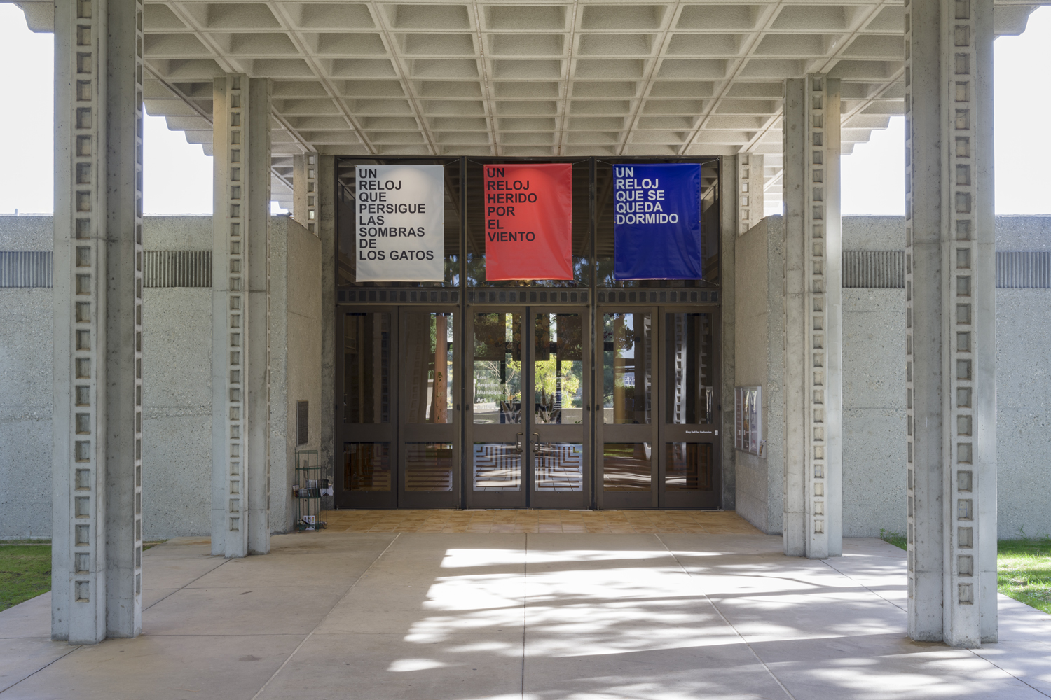 There are three artworks hanging from the ceiling by David Horvitz facing the doors outside of the art gallery. The left sign is white with black lettering that says