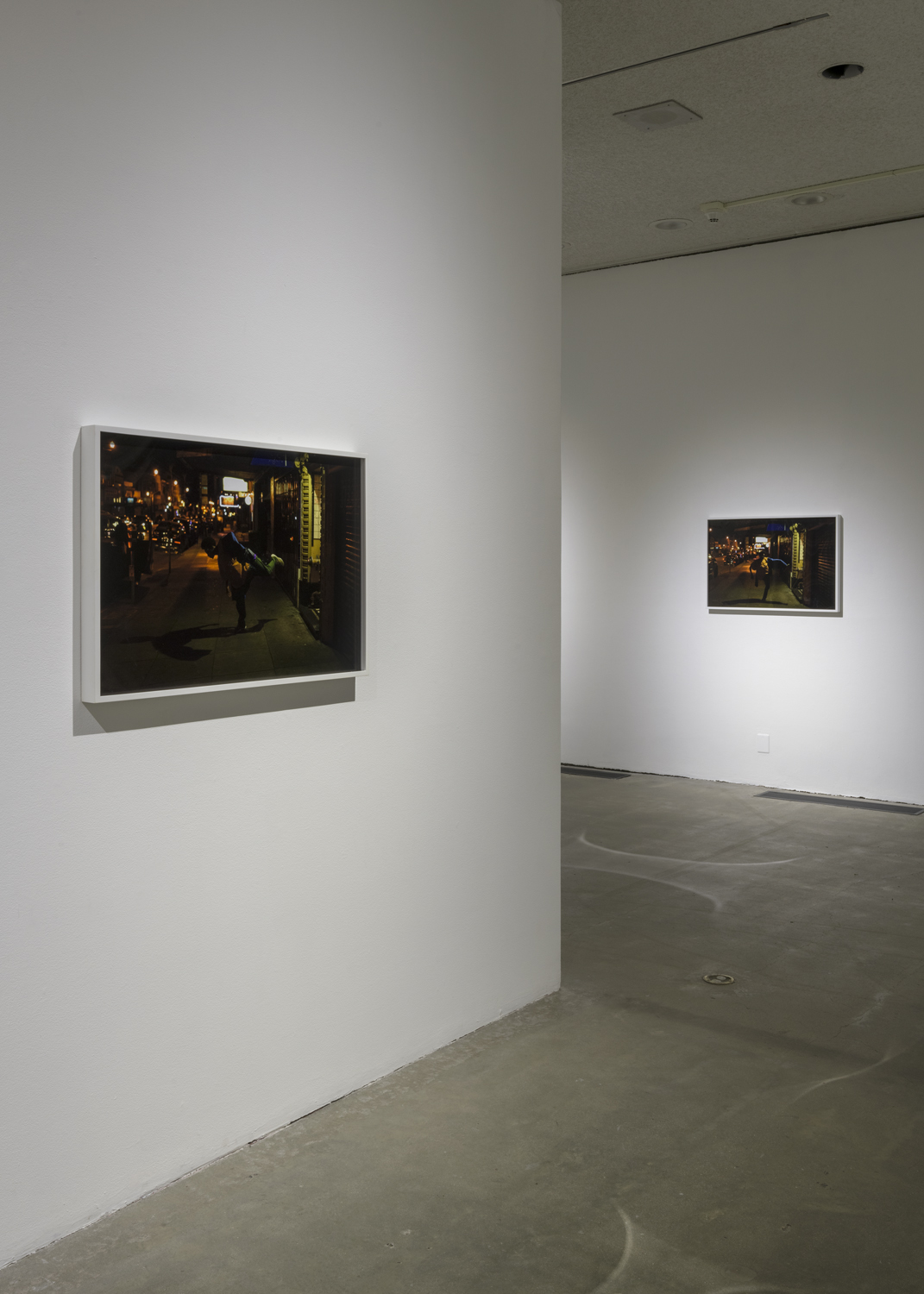 There is one large horizontal photograph hanging on the wall. The photograph is of a city street sidewalk at night. To the far right of this artwork is another artwork that is also a photograph of a similar city street sidewalk at night. These photographs are both by the artist Joshua Ross.