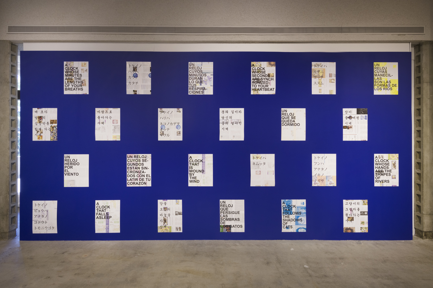 The art installation by the artist David Horvitz is comprised of a large, cobalt blue painted wall with twenty-four paper posters separated into four rows of six posters per row. The posters are hanging vertically and have various black lettering in different languages such as English, Spanish, Japanese and Korean.