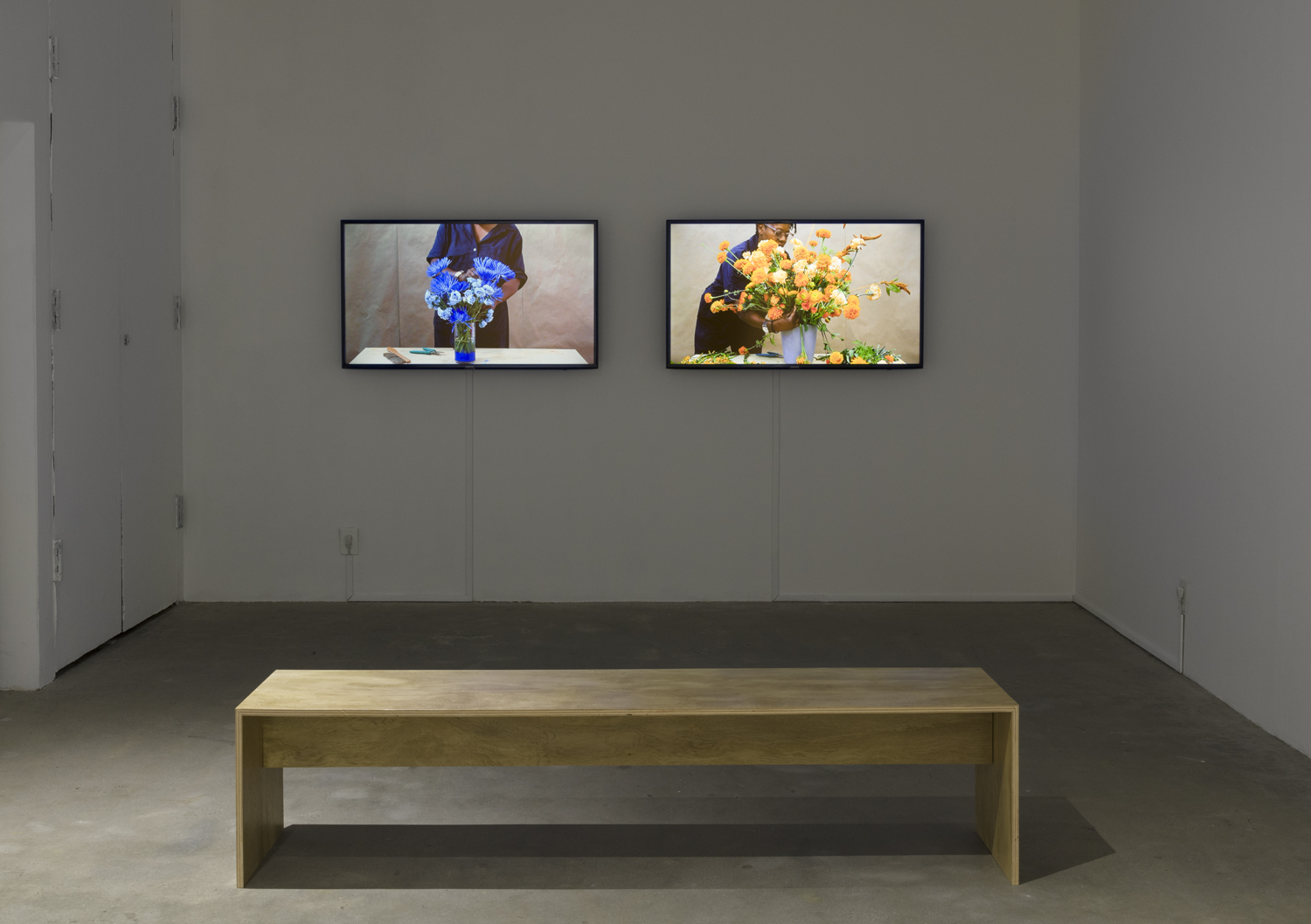 The video art installation by the artist Cauleen Smith is featured on two different television screens. On the left screen is a woman making a blue colored flower arrangement. On the right screen is the same woman making an orange colored floral arrangement. Both videos are by the artist Cauleen Smith.