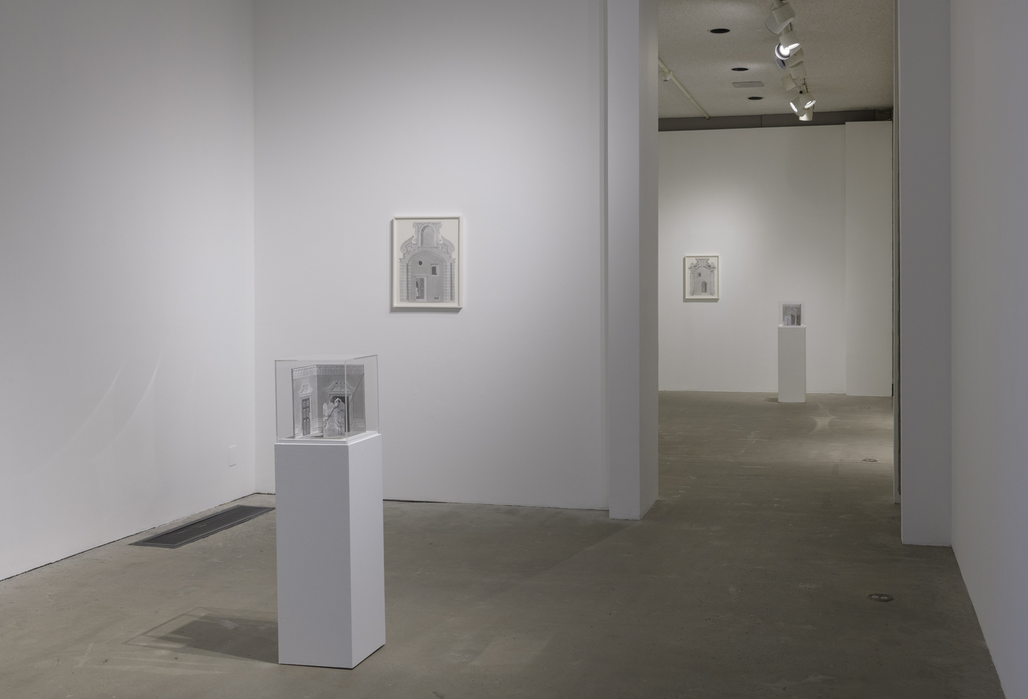 In this art installation by the artist Milano Chow, there is one artwork on a white pedestal with a plexiglass cover. Under the cover is a small graphite sculptural work featuring an architectural space and an upright partition with a figure peeking out from behind it. Behind this artwork is another graphite drawing of a different architectural space hanging on a wall. There are two other similar artworks placed in the next room behind these works.