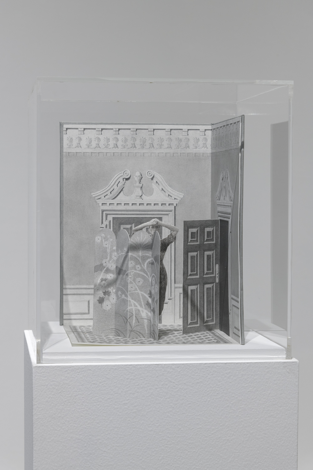 This artwork by the artist Milano Chow is small graphite drawing and sculpture of a room with one door closed and another opened. In the center of this room is a changing partition with a figure peeking out from behind it. The drawing and sculpture also includes a black and white checkered floor.