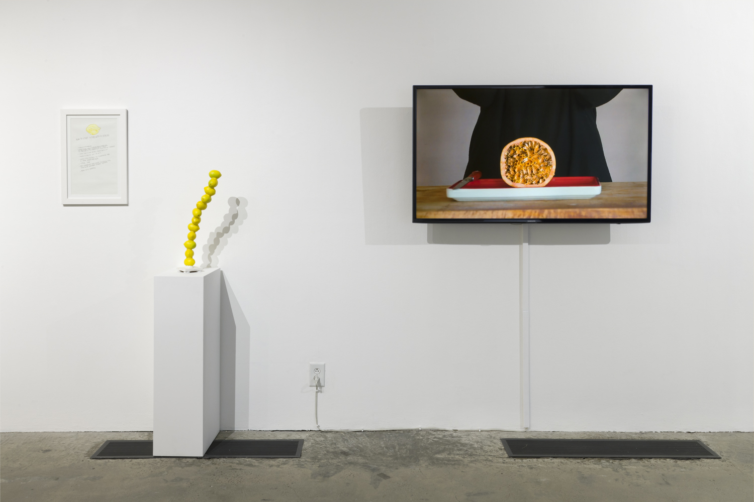 The artwork installation by the artist gloria galvez includes a print artwork hanging on the wall, a sculpture piece placed on a pedestal, and a video displayed on a mounted television monitor. The print artwork hanging on the wall includes indecipherable black text with a small yellow drawing. The sculpture is on a pedestal is to the right of this print. The sculpture is of a stack of twelve, small objects that look like lemons; this stack is slightly leaning to the right. To the right of this artwork is the video displayed on a mounted television monitor. The video still shows a figure clothed in black with a split open pomegranate on a white plate in front of them on a table.