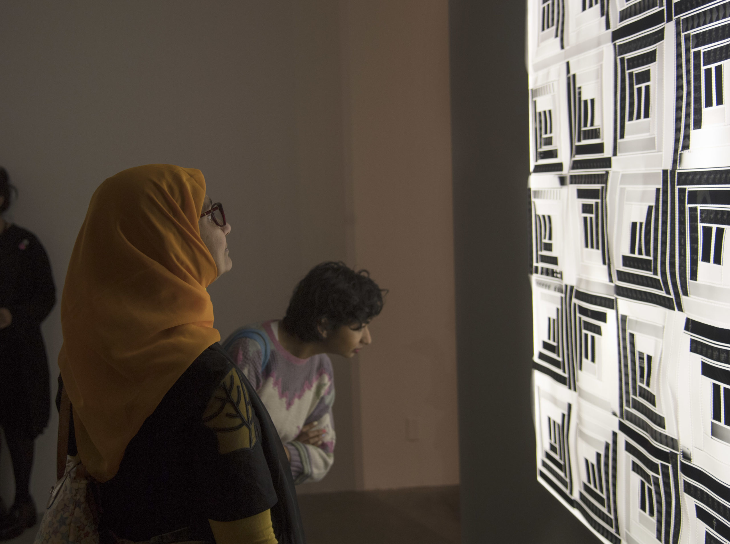 Two visitors are looking at a black and white sculptural work by the artist Sabrina Gschwandtner in the exhibition, COLA 2019.