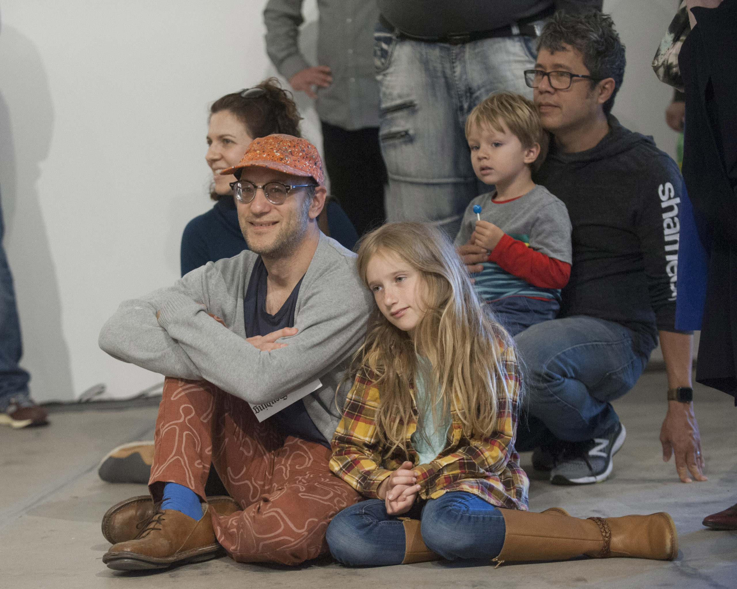 Visitors are sitting on the floor listening and watching a performance in the gallery.
