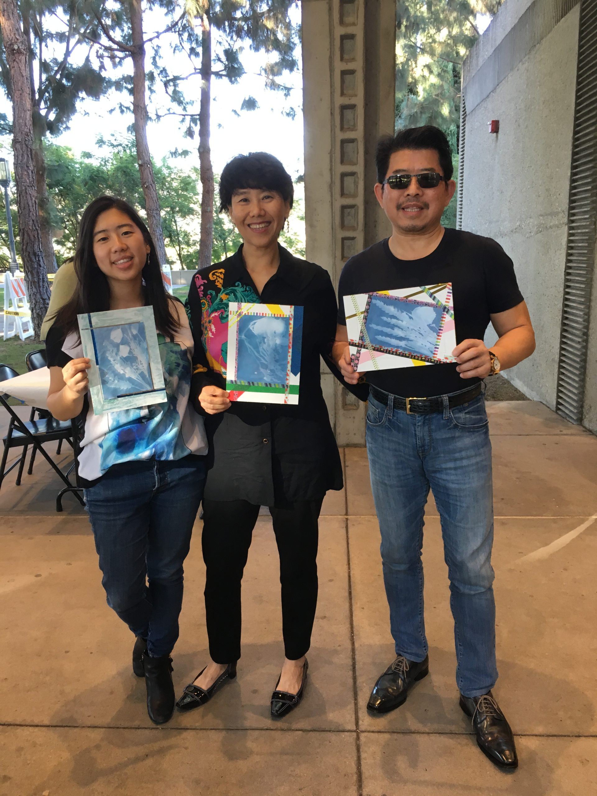 Three visitors are holding up their cyanotype artworks created during a public program.
