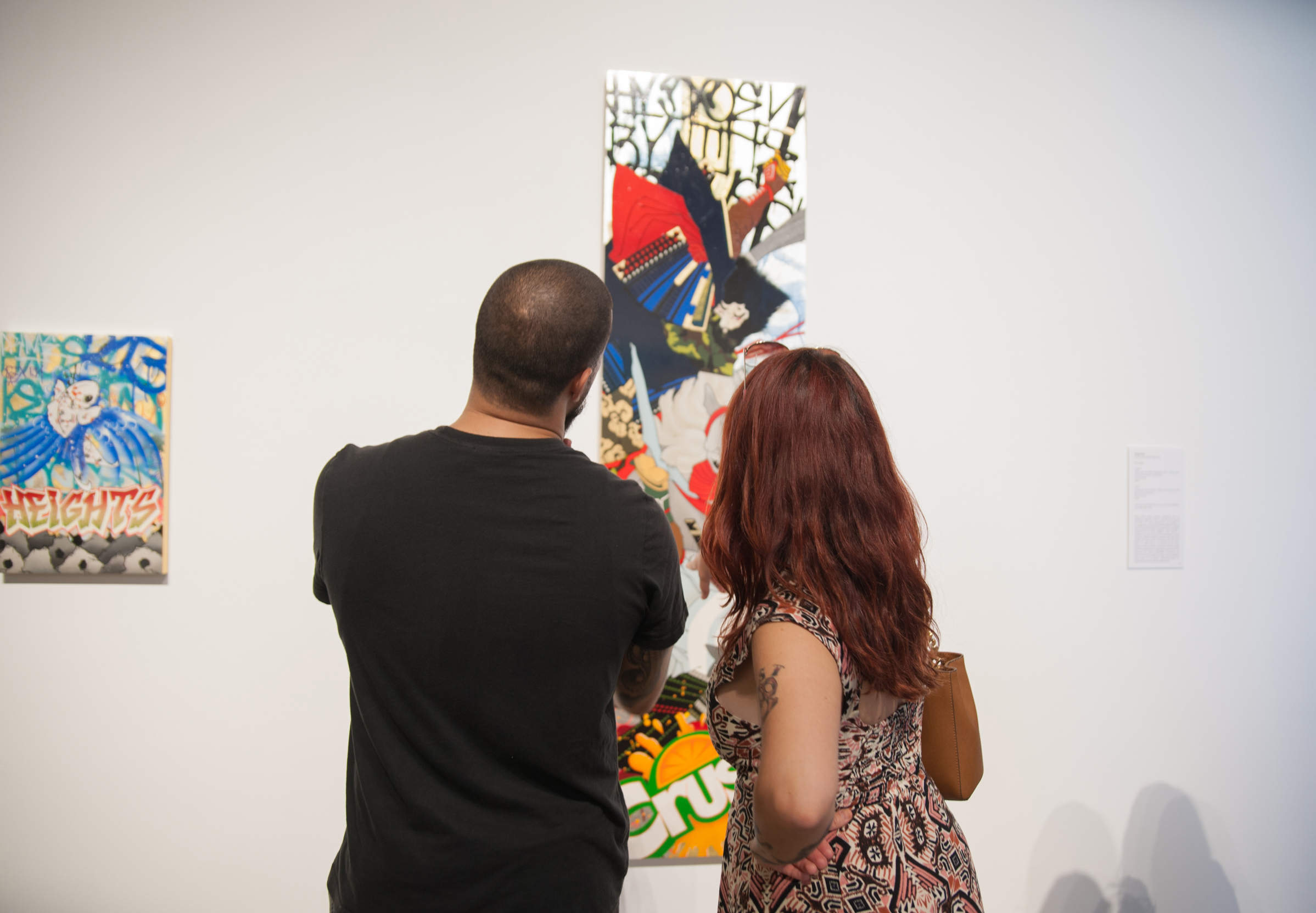 Two visitors are looking at a a colorful artwork by the artist Gajin Fujita in the exhibition, Here.