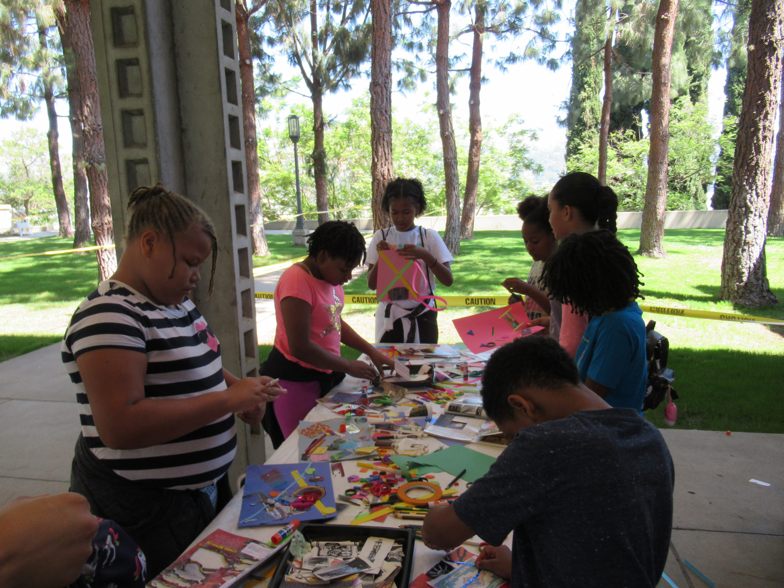 A group of seven young students are participating in an art-making activity involving bright colored paper, stickers, markers and other materials.