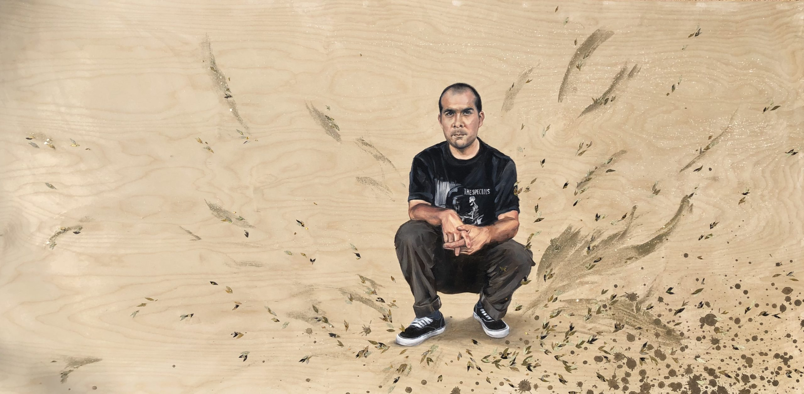This artwork by Shizu Saldamando depicts an individual of color swatting with his hands interlocked. He is wearing black and white sneakers, dark brown pants, and black t-shirt with the words The Specials on it. There are various, painterly marks surrounding the figure. The figure and marks are rendered on a light wood panel.