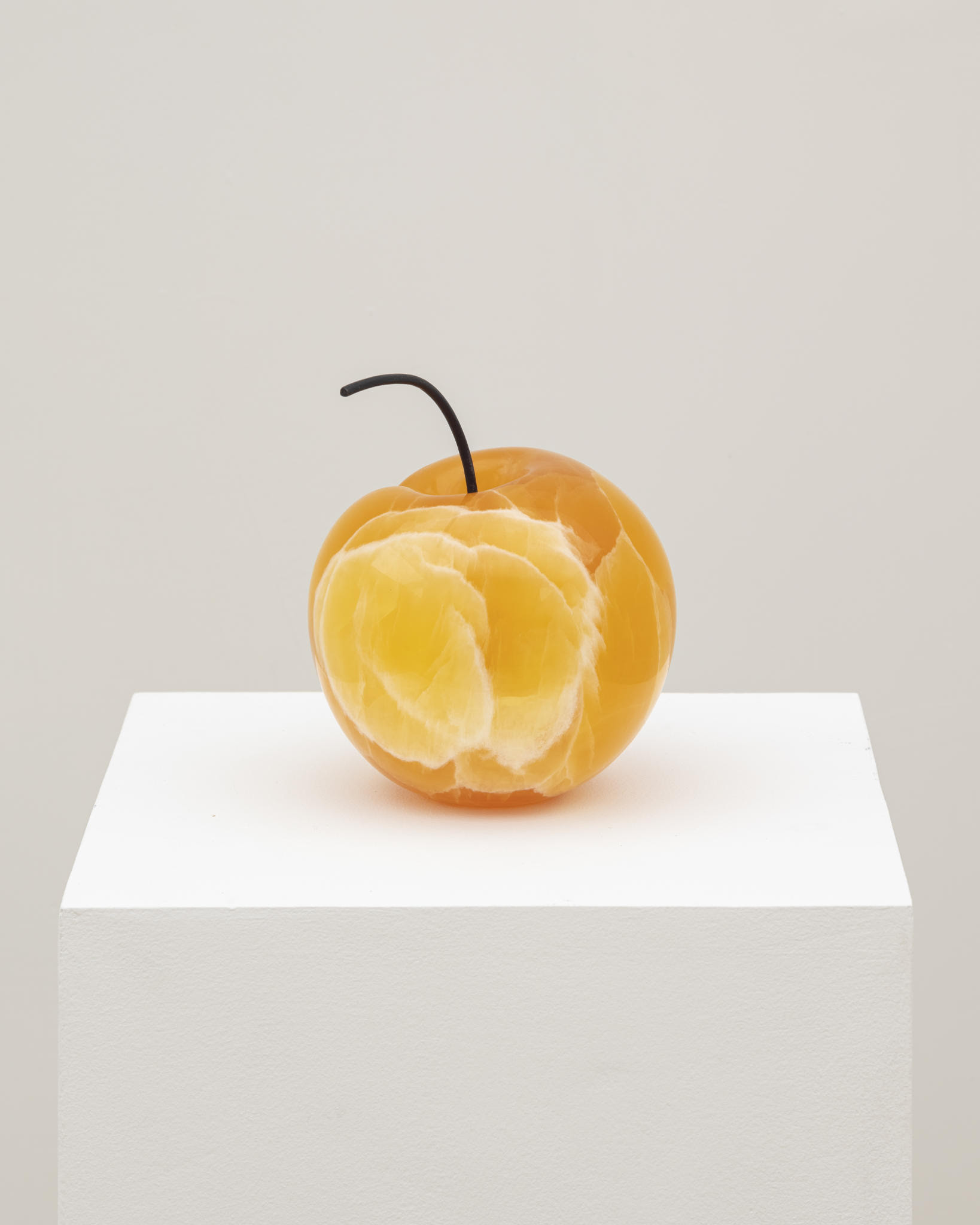 This artwork by the artist Nevine Mahmoud depicts an orange-colored peach sculpture placed upright on a white pedestal. The sculpture has various shades of orange, yellow and white, as well as a brown, slightly curled stem on top of the sculpture.