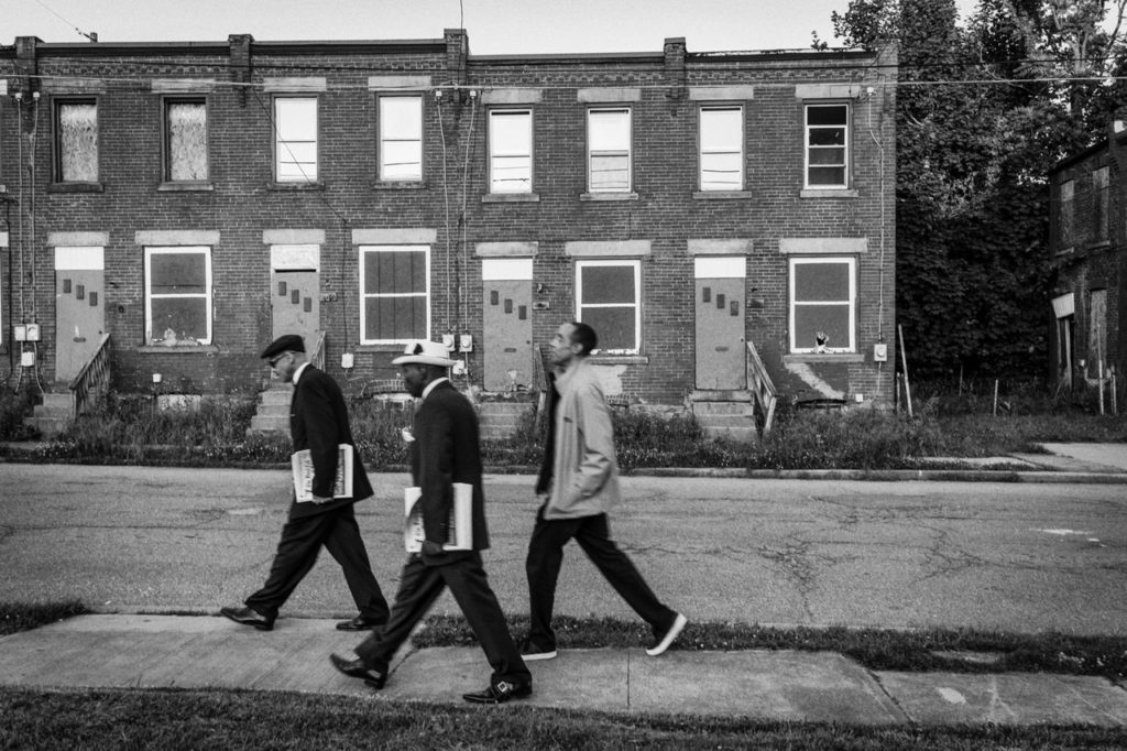 In this black and white photograph by Amir Saadiq, three Black men in the Nation of Islam are walking together on a sidewalk in front of a boarded up residential building. They are walking from right to left; two men are holding a stack of newspapers in their right arms and are wearing formal attire. The other man walking behind them has his hands in his jacket pockets and is wearing casual wear. This photograph is part of the artist's body of work titled It Takes a Nation.