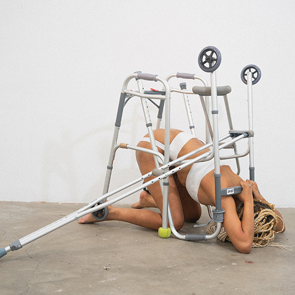 This is a color photograph of Panteha Abareshi. The artist is featured kneeling while bent over beneath silver crutches and a walker. The artist is using their arms to protect their head. Abareshi is wearing a white bodysuit and is performing in a white wall and grey cement floor space.