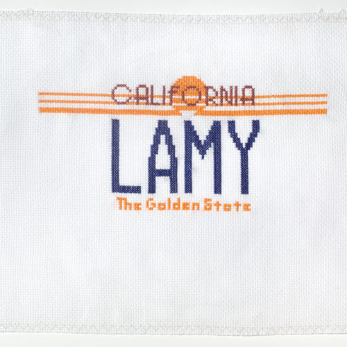 This is a color photograph of an embroidered fabric depicting a vintage California license plate by Phung Huynh. The white square fabric has motifs of a license plate in the center of the work, such as California written in all capital letters over a sun motif that has three yellow horizontal lines going through the letters. The plate name reads Lamy in dark blue capital letters. Below it reads The Golden State that is yellow in color.