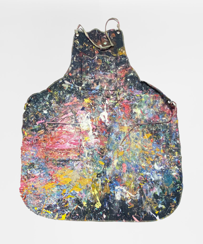 This is a color photograph of an apron owned by Vanessa McConnell. The apron is made of a dark-colored fabric, and it is covered in brightly colored paint splatters and strokes. The paint colors include pink, red, yellow, green, orange, blue, and white.