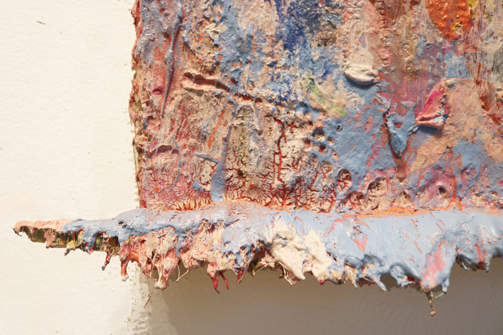This is a color photograph of a detail of an abstract painting by Vanessa McConnell. The image is a close-up of the bottom edge of the painting's canvas. It features thick layers of paint in various colors, such as blue, orange, and white. At the bottom of the canvas, there is a ridge of dried paint.