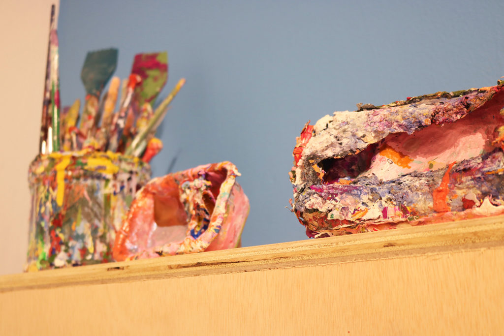 This is a colored photograph of some of Vanessa McConnell's studio ephemera. The image features three paint covered vessels, one which holds artist tools, such as paint-covered paintbrushes. The vessels sit on a wooden shelf that hangs from a light blue-colored wall.
