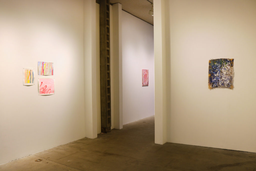 This is a color photograph of a room in the Los Angeles Municipal Art Gallery. The walls of the room are white-colored and lined with several abstract paintings by Vanessa McConnell.