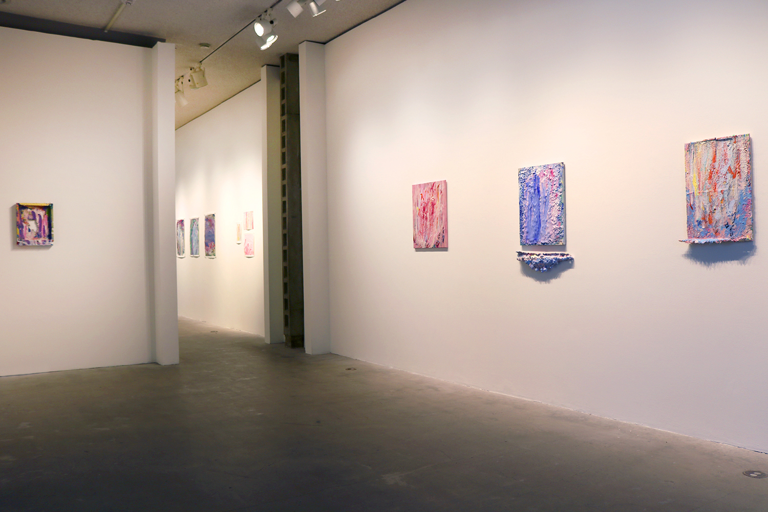 This is a color photograph of a room in the Los Angeles Municipal Art Gallery. The walls of the room are white-colored and lined with abstract paintings by Vanessa McConnell.