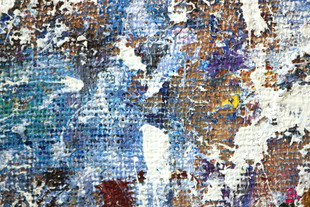 This is a color photograph of a detail of an abstract painting done on burlap by Vanessa McConnell. This painting features thick layers of paint of various colors, such as black, blue, and white. The texture of the burlap as well as some unpainted sections of burlap are visible.