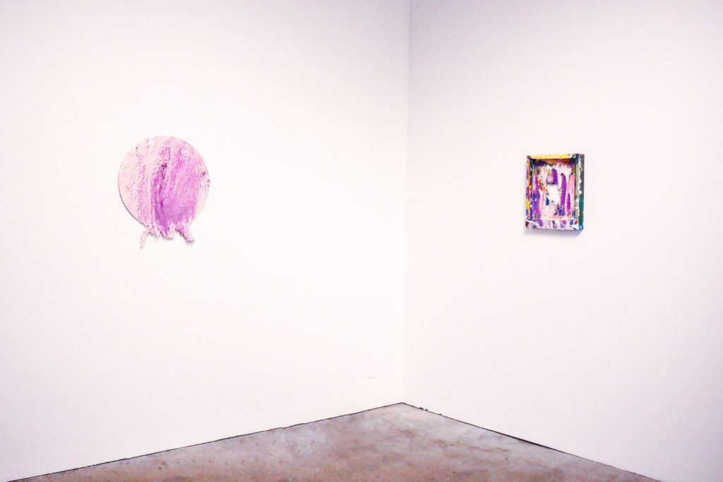 This is a color photograph of a corner of a wall in the Los Angeles Municipal Art Gallery. The wall on the left features an abstract painting by Vanessa McConnell. The painting is on a circular canvas and has thick layers of pink and purple colored paints. Extending from the bottom of the painting is a thick ridge of paint. The wall on the right features another abstract painting by Vanessa McConnell. This painting is on the backside of a rectangular canvas and has thick layers of paint of various colors, such as purple, pink, and green. There is a hole in the center of the canvas.