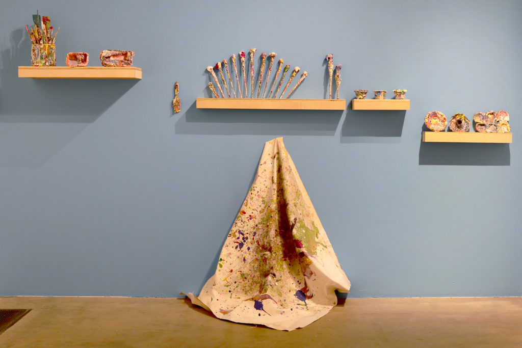 This is a color photograph of part of an installation of objects by Vanessa McConnell in the Los Angeles Municipal Art Gallery. The wall is painted sky blue and has wooden shelves that hold ephemera from McConnell's studio. The ephemera include paintbrushes and vessels that are covered in thick, dried paint. Below the shelves is a large piece of fabric splattered with dry paint.