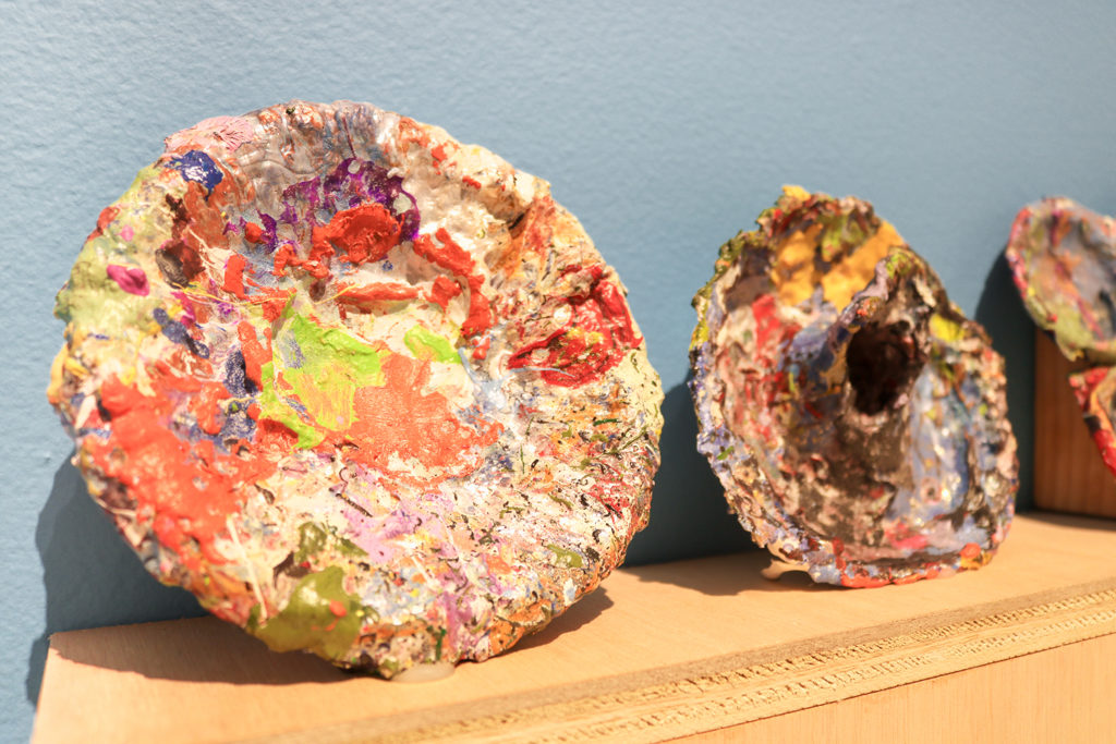 This is a colored photograph of vessels from Vanessa McConnell's studio practice. Three vessels are visible in the image and sit on a wooden shelf that hangs on a blue wall. The vessels are covered in thick layers of multi-colored paint.