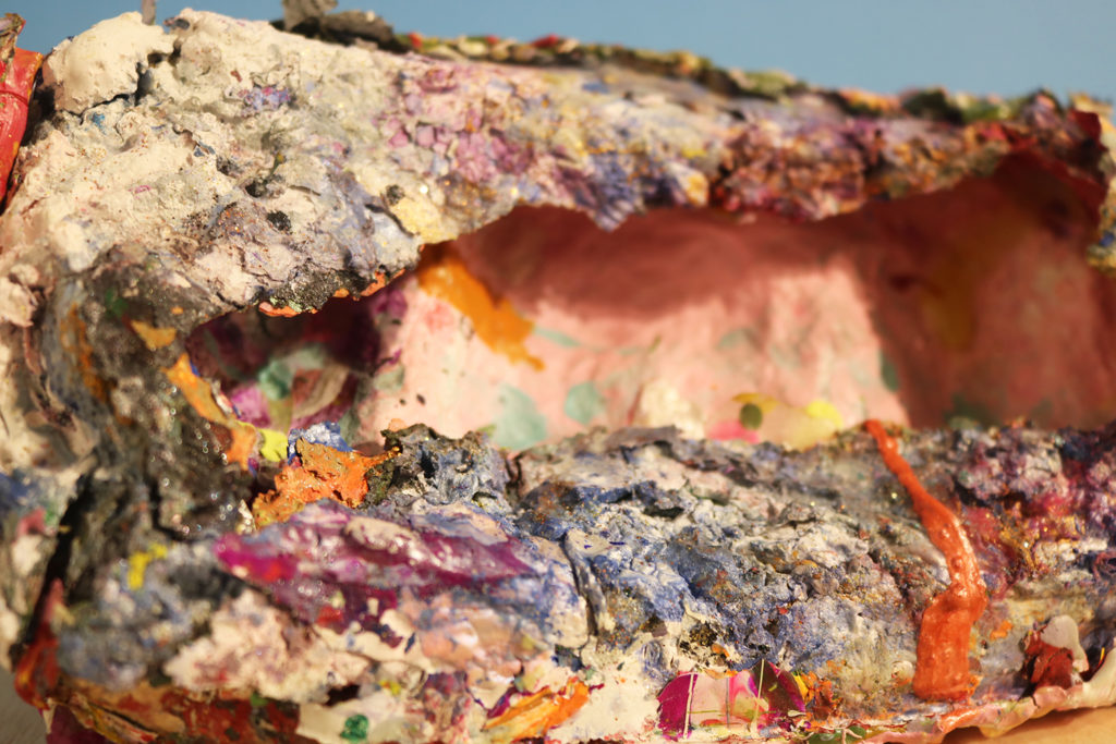 This is a colored photograph detail of a vessel from Vanessa McConnell's studio practice. The image is a close-up of the inside of the vessel, which is rectangular in shape and is covered in layers of multi-colored paint.