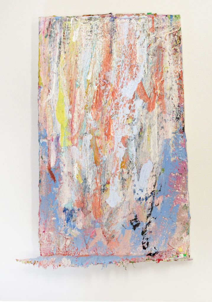 This is a color photograph of an abstract painting by Vanessa McConnell. The painting features thick layers of paint in various colors, such as blue, orange, white, yellow, and black. At the bottom of the canvas, there is a ridge of dried paint.