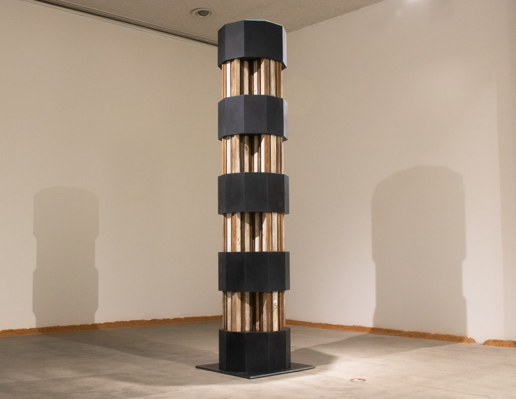 This is a color photograph of an artwork by Lukas Geronimas. The photograph depicts the sculptural work, Barnsdall Column. This work is constructed in nine segments, with four multi-paneled and colored wood components in the shape of a cross and five ten-sided prisms made of a custom resurfaced plexiglass in a dark grey-black color. The cross pieces are modeled after the LAMAG's unique column design. Placed on the floor along the wall is Puzzledust, which is sawdust that was produced, collected and stored by the artist over the past two years.