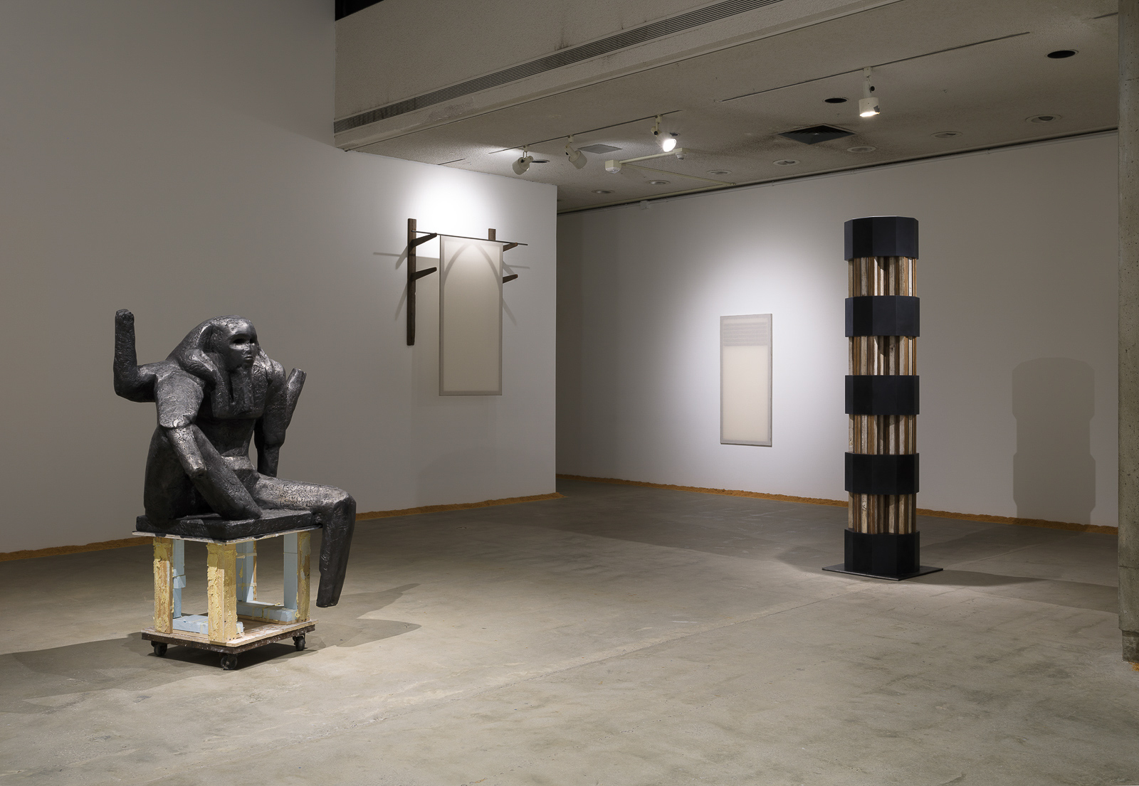 This is a color photograph of five artworks by Lukas Geronimas. On the left in the foreground is the sculpture Puzzlemaster, which is a sculpture of a dark grey seated figure on a wood pedestal placed on top of a dolly. To the right of this work is the sculpture Custom Hung Valance,which is a sculpture constructed of wooden racks and stretched muslin resembling a Gothic-style window. To the right of this work on a perpendicular wall in the background is the artwork Custom Vent,which is hung sculpture made of muslin and plywood resembling a vent on a wall. On the far right in the middle ground is the sculpture Barnsdall Column, which is constructed in nine segments with four multi-paneled and colored wood components in the shape of a cross and five ten-sided prisms made of a custom resurfaced plexiglass in a dark grey-black color. The cross pieces are modeled after the LAMAG's unique column design. Along the perimeter of the floor and walls of this installation is another artwork titled Puzzledust, which is sawdust that was produced, collected and stored by the artist over the past two years.