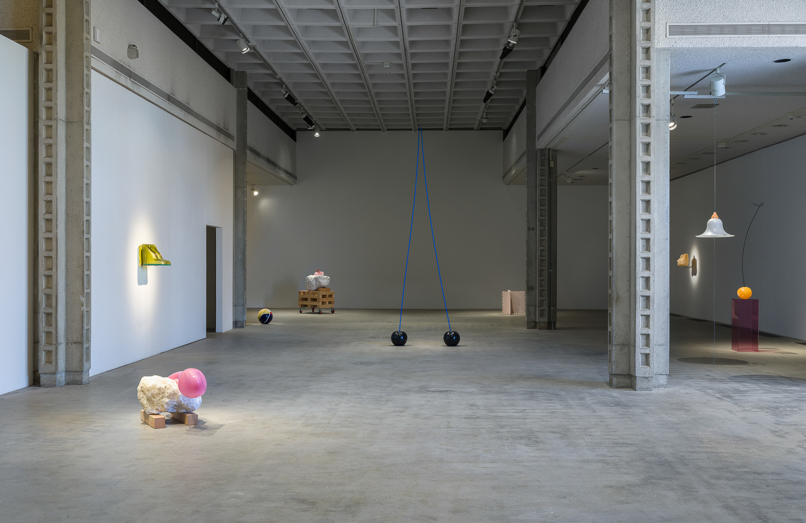 This is a color photograph of an installation view of artworks by Nevine Mahmoud. Pictured left to right are: a sculpture titled HOT TOY STRADDLE, which is a large white boulder with a pink object placed on top and sitting on the floor; a sculpture titled Bust (lagoon) installed on the adjacent wall, which resembles a bare female chest made from hand blown glass and resin in a yellow-green color; a sculpture titled Beach Ball IV in the background, which is a spherical ceramic work, cracked in a few places, painted with pink, yellow, red, and blue glaze made to appear like an inflated beach ball; a sculpture titled Three Components, which is a large white boulder with a light pink object placed on top and sits on top of a wooden crate; a sculpture titled Aileen & Elvis, which resembles a two-stemmed black cherry with blue stem; a sculpture titled Castle component #1, which resembles two, light pink colored puzzle pieces criss-crossed; a sculpture installed on the adjacent wall titled Babette, which resembles a bare female chest in a peach-tan skin color made from hand blown glass, resin, and aluminum; a sculpture titled Sherry which depicts a bright orange-red colored cherry shaped sculpture placed on top of a fuschia colored plexiglass pedestal; and a hung sculpture titled Breast shade, which resembles a bare female breast made from alabaster and pigmented resin.