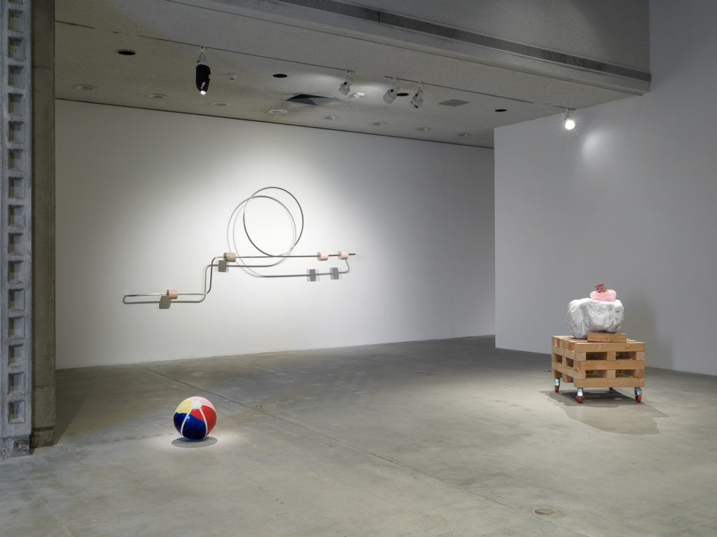 This is a color photograph of three sculptures by Nevine Mahmoud. Pictured left to right are: a sculpture titled Beach Ball IV, which is a multi-colored spherical ceramic work placed on the floor and resembles an inflatable beach ball; a wall-mounted sculpture titled Abacus arm 1, which features a linear steel bar with a circle and four stone components. Each of these components are wrapped around the steel bar and are different stones, such as onyx, Portuguese marble and Aphrodite marble; and a sculpture titled Three Components, which includes a large white boulder with a small, pink, bulbous glass object that has a red coil placed on top of it. These particular elements sit on top of a large stack of wood pieces on wheels.